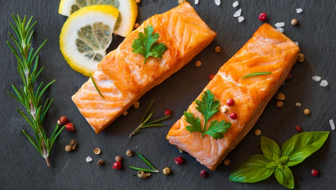 Cooked salmon fish fillet with pepper, lemon and herbs