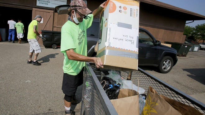 Jeff Smith dumps recyclables into a bin at the Jackson Township Recycling Center earlier this month. The organization, which thought it would have to close, made some changes in its operation and remains open. IndeOnline.com file photo / Kevin Whitlock)