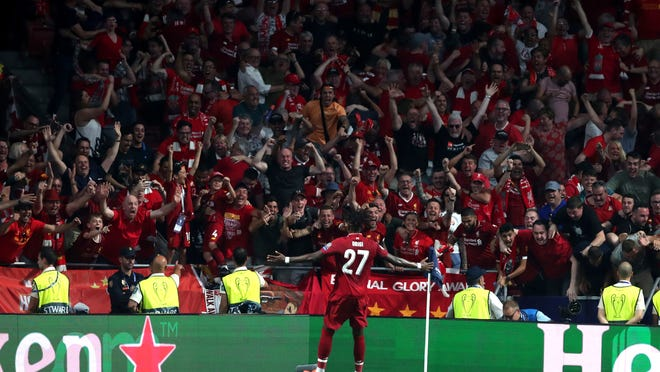 Liverpool's Divock Origi celebrates with his fans after scoring his sides second goal during the Champions League final soccer match between Tottenham Hotspur and Liverpool at the Wanda Metropolitano Stadium in Madrid, Saturday, June 1, 2019. (AP Photo/Francisco Seco)