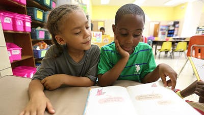 Malachi Williams-Mingo, left, and Donte Hayes read in Pam Stein's combined first- and second-grade class at Cincinnati Generation Academy. The charter school is in the former North Fairmount School that was also home to the East End Community Heritage Academy.