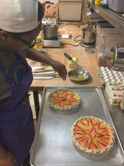 BreAsia Washington, a student at the CC Pearce Culinary School, with a passion for baking, makes lemon chess pies with fresh strawberries for the Bakery at Project Host.