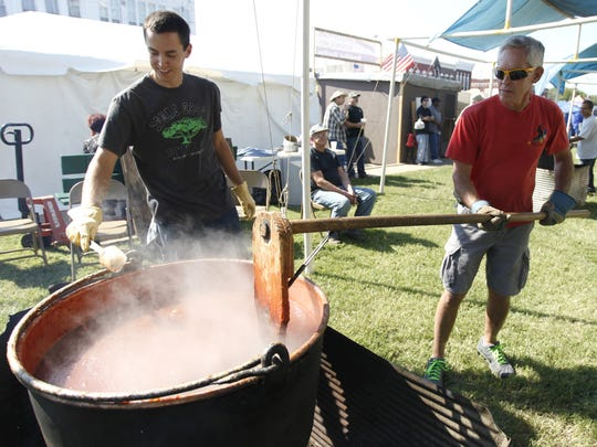 Mike Cravers, right, uses a paddle to stir a pot of apple butter as Brian Adams uses a spoon to scrape the sides of the copper kettle last year during Apple Butter Makin' Days on the square in Mount Vernon.