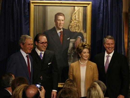George W. Bush, left, smiles for a picture next to