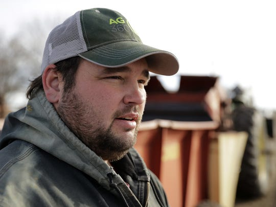 Matt Ubell pauses from feeding cattle on his farm near