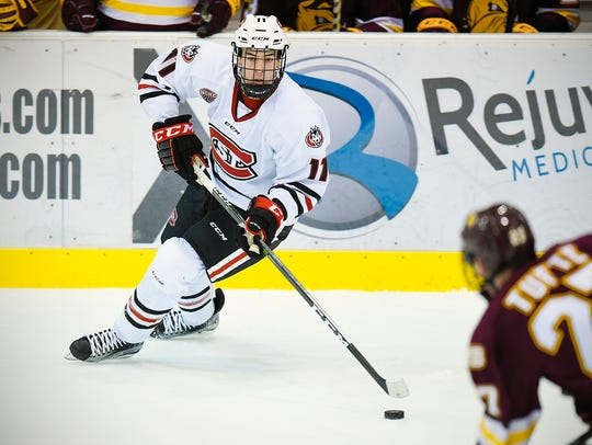St. Cloud State's Ryan Poehling, 11, skates the puck