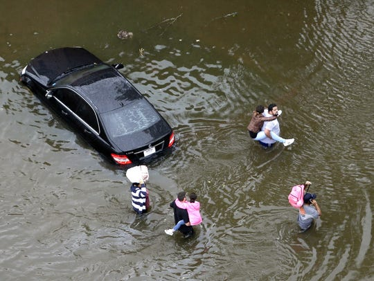 Residents wade through floodwaters as they evacuate