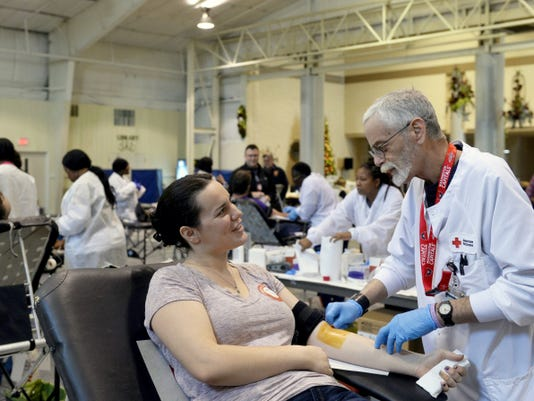 Rose Heil of Hopewell Township and American Red Cross nurse Eric Smith make small talk as Smith swabs her arm with iodine at a blood drive on at Grace Fellowship Church. The blood drive was hosted in memory of Zac Sweitzer and Rodney Miller, who were good friends and volunteer firefighters until they lost their lives in 2008 and 2013, respectively.