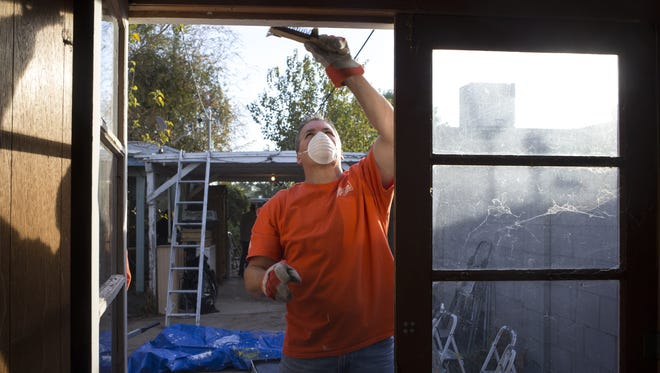 Dave Mitch (Home Depot volunteer) scrapes off paint on the home of veteran Claudena Lehr, Dec. 12, 2017, during Home Depot's annual Celebration of Service campaign.