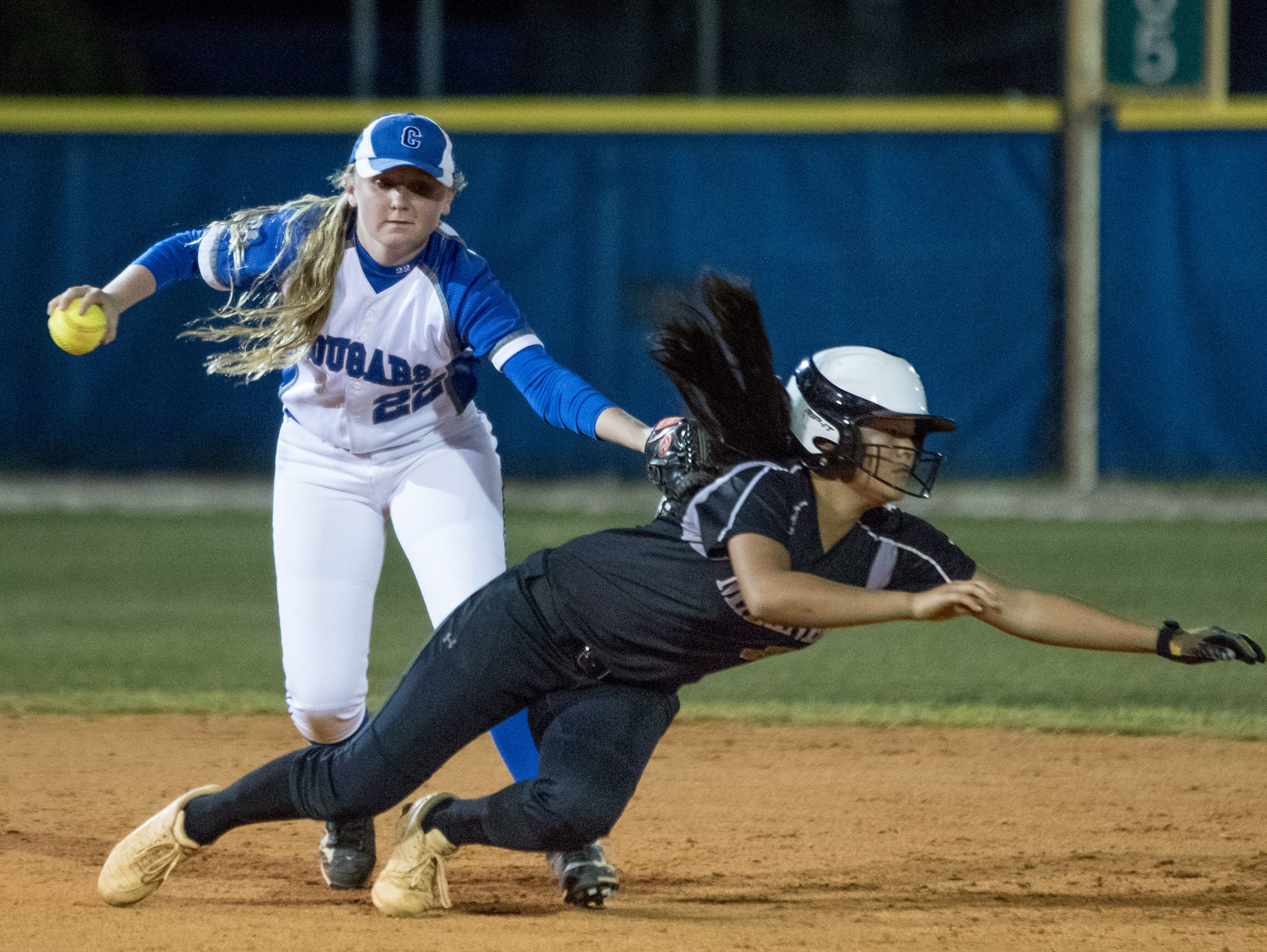 Mariner's only run scores as Barron Collier H.S.'s shortstop Megan Scoone (22) tags Mariner H.S.'s Abby Love (8) with a balless glove as she dives back to second base during the class 6A regional softball quarterfinal game at Barron Collier High School in Naples, FL on Wednesday, April 20, 2016. (Photo by Gregg Pachkowski/Special to the Daily News)