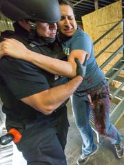 Las Cruces Fire Department driver operator Robert Galaz, helps Las Cruces Police officer Connie Heard, who is acting as a victim on Wednesday, March 30, 2016, during a LCPF and LCFD combined active shooter training. Las Cruces firefighters are now uniformed with new ballistic gear to keep them safe when entering dangerous enviornments to help save more lives.