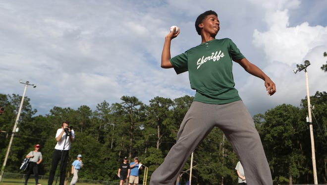 Easias Bass, 13, throws out the first pitch after speaking to the crowd gathered for the Ribbon-cutting ceremony of newly refurbished Capital Park baseball field that received a grant from the Scotts Field Refurbishment Program and Major League Baseball.
