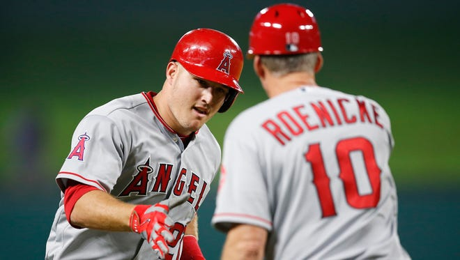 Angels center fielder Mike Trout (27) celebrates a home run with third base coach Ron Roenicke earlier this season.