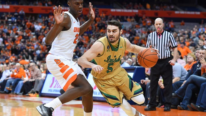 Notre Dame Fighting Irish guard Matt Farrell (5) dribbles the ball around past Syracuse Orange forward Tyler Roberson (21) during the first half at the Carrier Dome.