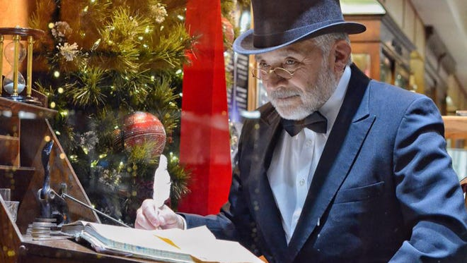 "Ebenezer Scrooge writes at his desk in a ""Living Windows"" display during Ripon's Dickens of a Christmas weekend."