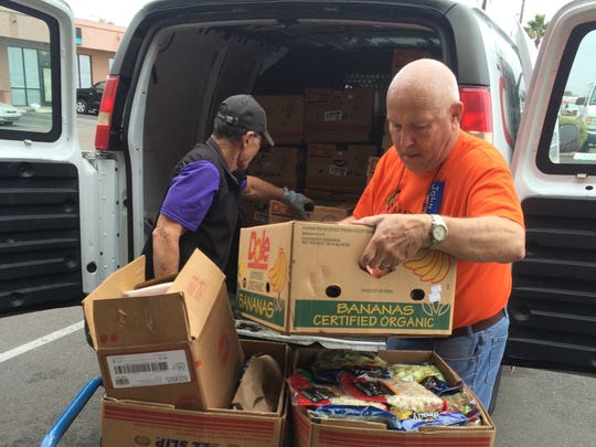 Gary Stuckey (left) and John Hansberry unload boxes of produce and meat from a local donor at Matthew's Crossing Food Bank in Chandler.