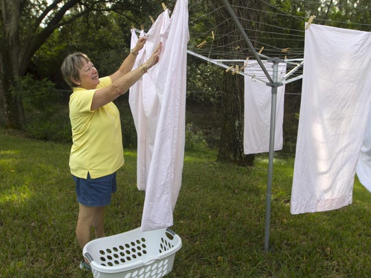 Terri Krass checks her sheets on the clothesline in her back yard in south Fort Myers on Wednesday.