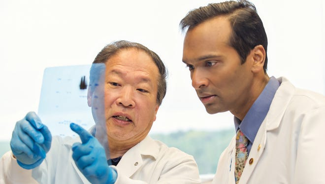 Dr. Arul Chinnaiyan,  right, a cancer pathologist and director of the Michigan Center for Translational Pathology, works with Fu-Zon Chung, a research laboratory assistant, at University of Michigan in Ann Arbor.