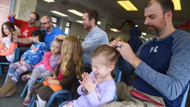Sophia Amspacher, 4, reacts as her dad, Erik, puts her hair in a ponytail during the Daddy Daughter Hair Boot Camp in Glatfelter Memorial Library on March 25.