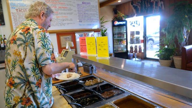 Bravo Burritos co-owner Bill Ellenbecker puts together a plate.
