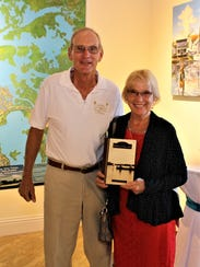 George and Carol Engstrom holding their autographed