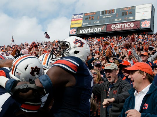 Auburn defensive lineman Marlon Davidson (3) and Auburn defensive back Daniel Thomas (24) embrace Auburn defensive back Nick Ruffin (19) after he return an interception for a touchdown during the NCAA football game between Auburn and Louisiana Monroe on Saturday, Nov. 18, 2017, in Auburn, Ala.