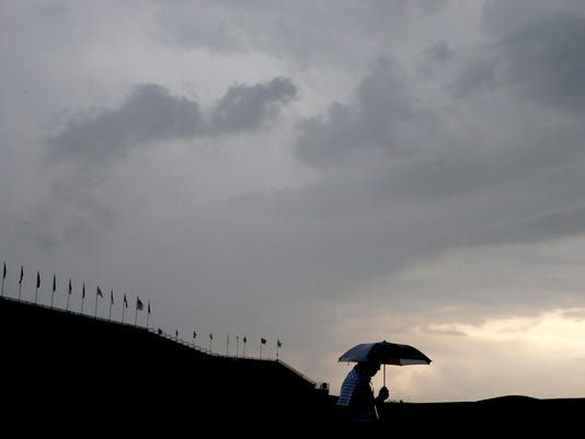 A fan leaves the course during the third rain delay in the first round of the U.S. Open golf championship at Oakmont Country Club on Thursday, June 16, 2016, in Oakmont, Pa. (AP Photo/John Minchillo)