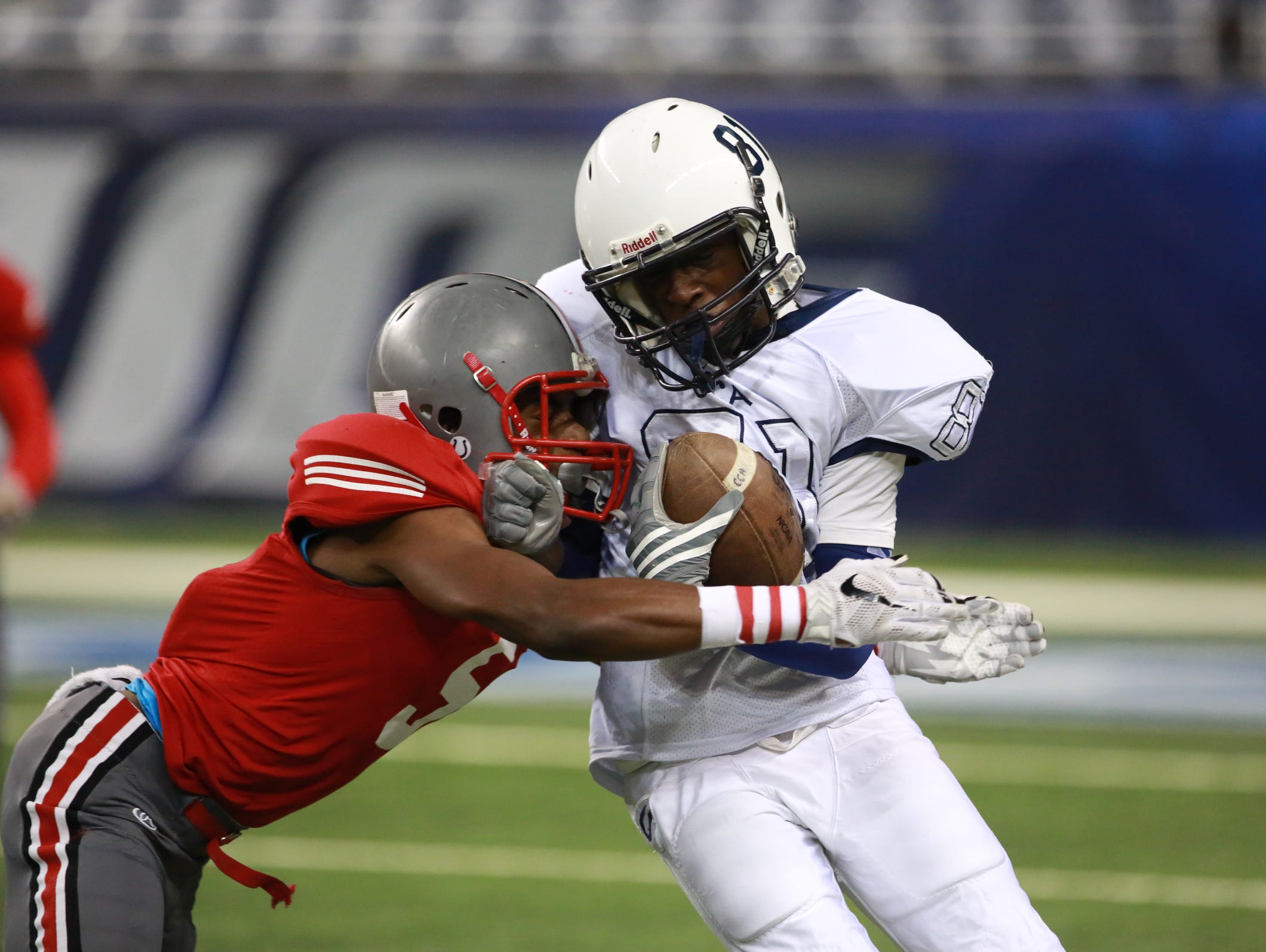 Detroit Central's Trevian Hill runs with the ball against Northwestern's Lamar Perdue, in the first quarter of the Detroit PSL Division II game at Ford Field Friday.