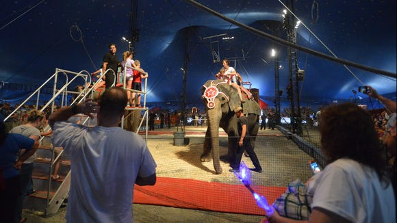 Circus goers ride an elephant under the big top during intermission for the afternoon show of Cole Brothers Circus at Augusta Expo in Fishersville on Tuesday, Sept. 2, 2014.