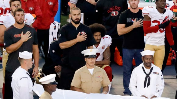 San Francisco 49ers quarterback Colin Kaepernick, middle, kneels during the national anthem before the team's NFL preseason football game against the San Diego Chargers, Green Beret Nate Boyer, who has met with Kaepernick, is at the quarterback's left.