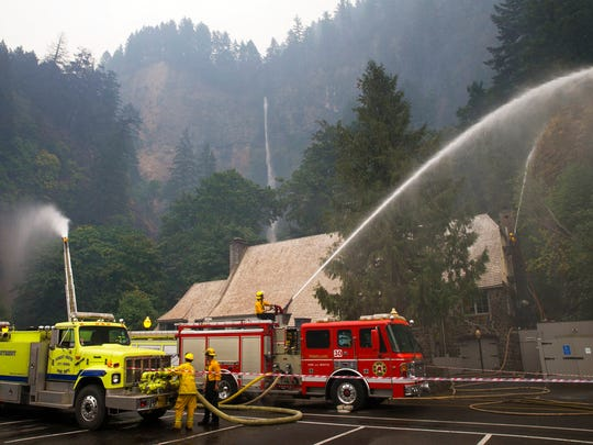 Firefighters maintain a vigilant watch at Multnomah Falls Wednesday Sept. 6, 2017 as the Eagle Creek Fire continues to burn east of Troutdale, Ore.