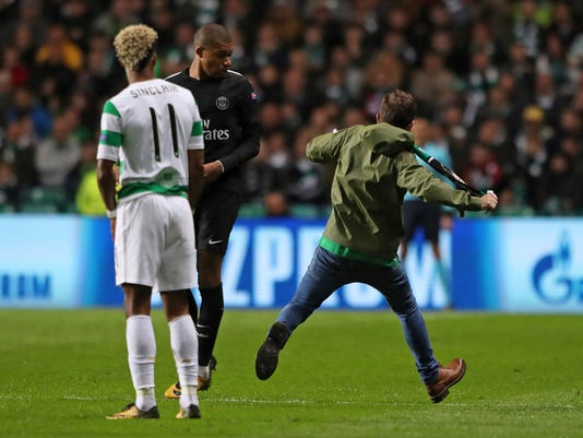 A fan runs by Paris Saint-Germain's Kylian Mbappe-Lottin, with Celtic's Sinclair, left, during the Champions League, Group B soccer match at Celtic Park in Glasgow, Scotland, Tuesday Sept. 12, 2017. (Andrew Milligan/PA via AP)