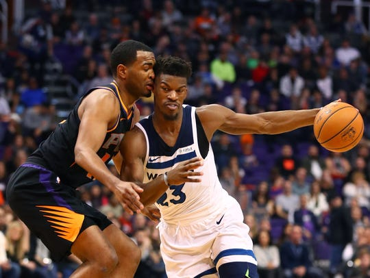 Jimmy Butler drives to the basket against Suns forward T.J. Warren during a game at Talking Stick Resort Arena.