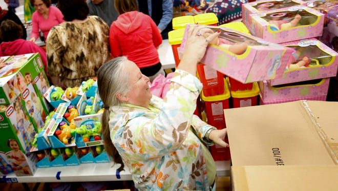 WyEdna McCabe, a family advocate for Head Start, restocks a girls gift pile Wednesday at the Arctic League in Elmira while assembling large gift bags. Arctic League annually fundraises to purchase gifts for needy children in Chemung County.