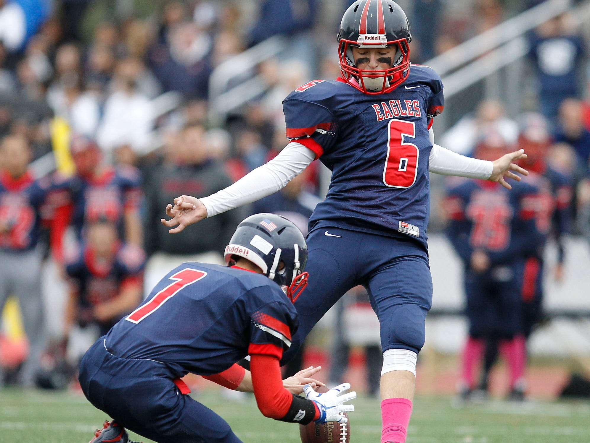 Eastchester's Jacob Risi (7) holds the ball as kicker Aidan Clemente (6) kicks an extra point during a varsity football game against John Jay Cross River at Eastchester High School on Saturday, Oct. 24, 2015.