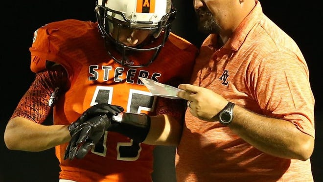 Robert Lee head football coach Shay Avants works with the Steers' Matthew Curry on a play call against the Santa Anna Mountaineers in a 2016 game.