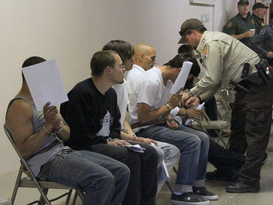 Several people wait to be processed at the Otero County Fairgrounds after being arrested for alleged narcotics charges early Friday morning.