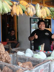 J. San Nicolas, 26, poses at his family's produce stand
