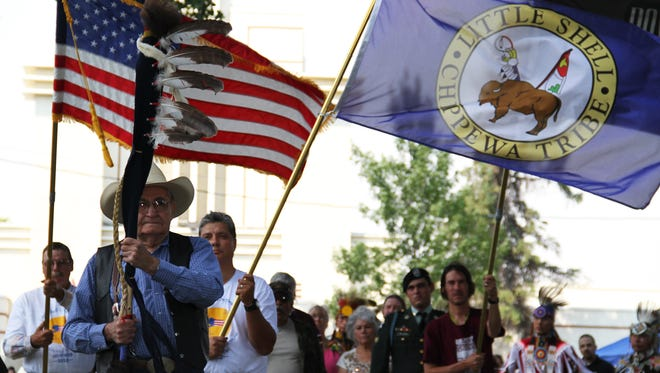 Little Shell Chippewa tribal war veterans carry flags during the opening ceremony of the powwow.