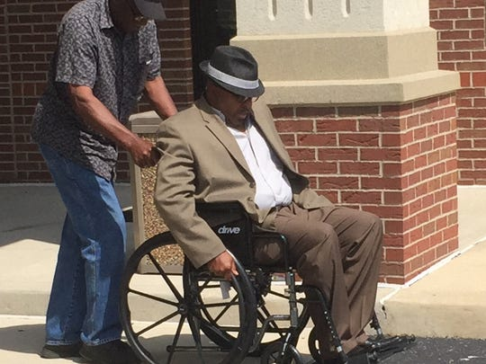 Carl Williams, shot by police earlier this week after calling 911 to report a carjacking attempt on his wife, is wheeled out of a church where he spoke to members of the media on Friday.