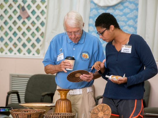 Alan McCoy and Danielle Blackman check out a piece on display July 21 at the Artistic Woodturners of Northwest Florida's meeting.