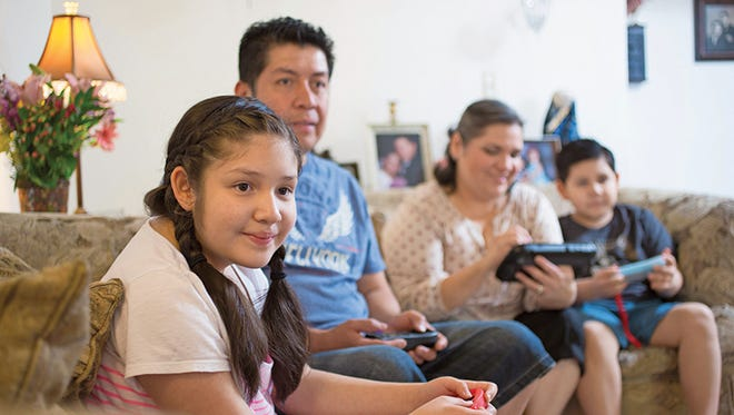 The Lopez family -- Elisa Marie, 11, dad Carlos, mom Alicia and Emilio, 8 -- play a video game at their Phoenix home as part of the children's unschooling experience.