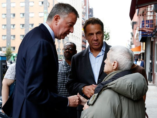 New York Mayor Bill de Blasio, left, and New York Gov. Andrew Cuomo  talk with area residents Sunday, Sept. 18, 2016, while touring the site of an explosion that occurred on Saturday night in the Chelsea neighborhood of New York. Numerous people were injured in blast, and the motive, while reportedly not international terrorism, is still being investigated.  (Justin Lane/EPA via AP, Pool)