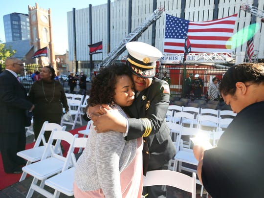 Kanisha Dawson, daughter of fallen firefighter Rodney Eddins, is comforted by Melanie Moody, manager of fire communications following the Memphis Fire Department's annual memorial service held in the courtyard at the Fire Museum.
