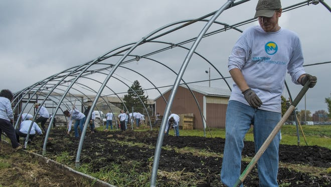 Justin A. Hinkley from the Lansing State Journal, turns over the soil in the hoop house at the Southside Community Center in Lansing as part of Make a Difference Day Saturday.