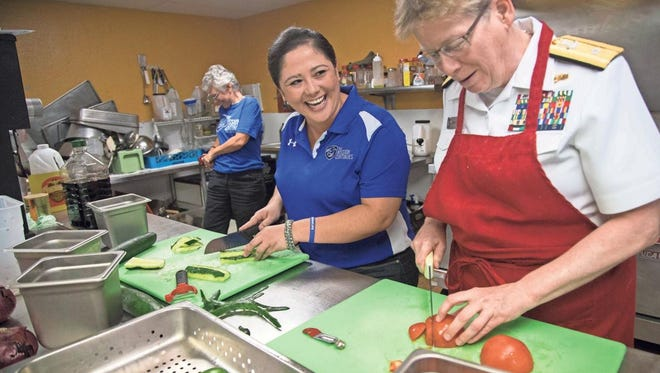 Rachel Gutierrez (center), service platoon leader for the Mission Continues' Phoenix division, and Rear Adm. Sandra Adams (right) are among the volunteers preparing dinner Monday for homeless vets at the MANA House in Phoenix. The facility houses 50 veterans daily.