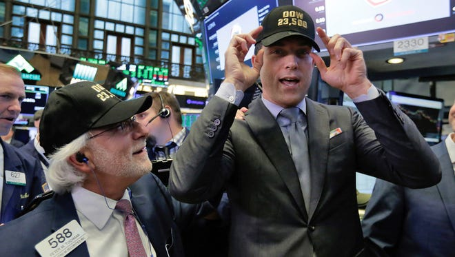 """In this Nov. 1, 2017 photo, trader Peter Tuchman, left, and New York Stock Exchange President Tom Farley don caps marking """"Dow 23,500,"""" on the trading floor as the index crosses the milestone. The stock market may have appeared to Donald Trump as """"a big bubble"""" before he was elected, but he's had plenty of reasons to tout Wall Street's gains as president. In the year since Trump's election, the Standard & Poor's 500 index has notched at least 60 record highs and risen 21.1%."""