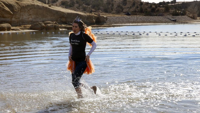 Erin Elledge, a member of Mountain Dental's Frozen Fairies team, exits Farmington Lake Saturday after taking part in the annual Polar Plunge,
