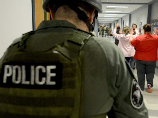 Jackson State Community College students walk down the hallway under Jackson police SWAT supervision Monday during an active shooter simulation.