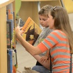 Brandy Morrow selects some books with her son Parker during a Sept. 12 visit to the Novi Public Library.