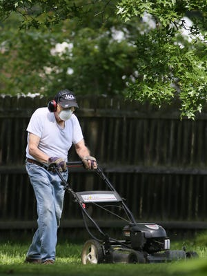 A man mows his yard in his Northwest Akron neighborhood. A combination of cold and warm spring with grass and tree and ragweed pollen all blooming at the same time adds up to a bad allergy season.